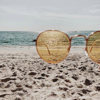 Bela praia tropical com areia branca, degraus, mar azul e óculos de sol amarelos ensolarados. viagem de verão ou conceito de férias
