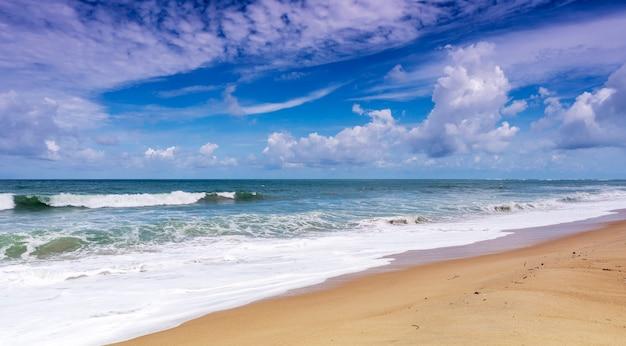 Bela praia tropical com oceano azul e fundo de céu azul e onda batendo na costa arenosa