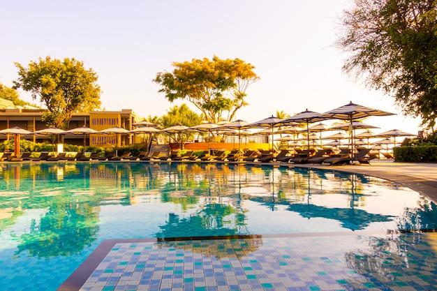 Bela praia tropical e mar com guarda-chuva e cadeira ao redor da piscina no hotel resort para viagens e férias