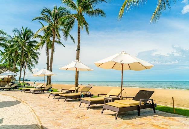 Bela praia tropical e mar com guarda-sol e cadeira ao redor da piscina em hotel resort para viagens e férias