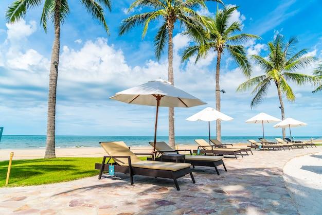 Bela praia tropical e mar com guarda-sol e cadeira ao redor da piscina em hotel resort