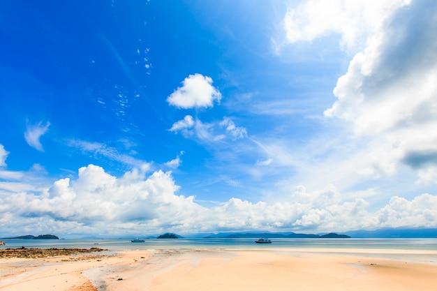 Bela praia tropical e mar em dia de céu de verão
