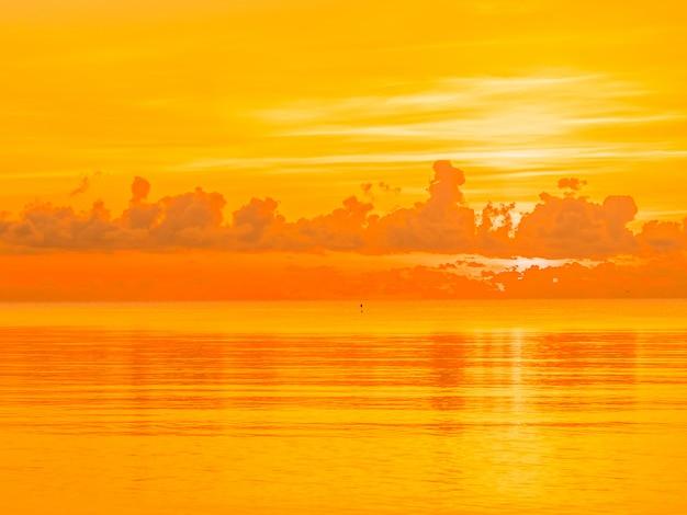 Bela praia tropical e mar oceano paisagem com nuvens e céu no nascer do sol ou por do sol