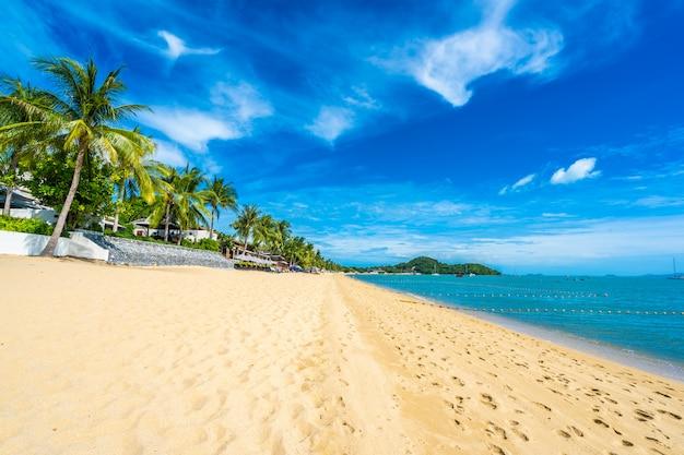 Bela praia tropical mar e oceano com coqueiro e guarda-chuva e cadeira no céu azul
