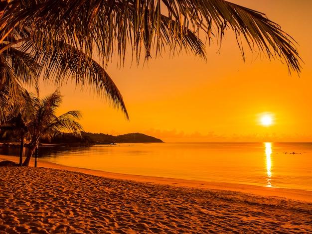 Bela praia tropical mar e oceano com palmeira de coco na hora do nascer do sol