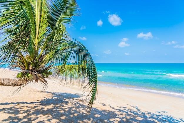 Bela praia tropical mar oceano com palmeira de coco ao redor de uma nuvem branca de céu azul para o fundo de viagens de férias