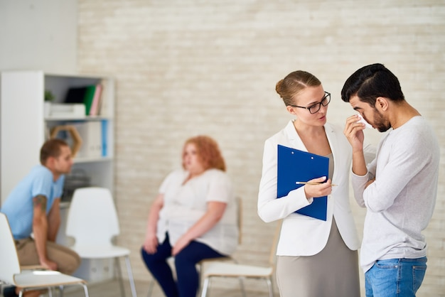 Bela psiquiatra consultoria chorando jovem
