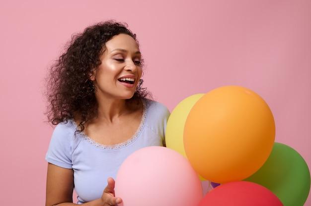 Bela raça mista com jovem de cabelos encaracolados regozijando-se, posando contra um fundo colorido rosa com bolas de ar coloridas. festa de aniversário, aniversário, celebração, conceito de eventos com espaço de cópia