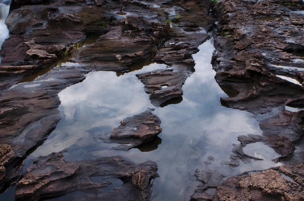 Bela refletir rocha e água com a floresta circundante.