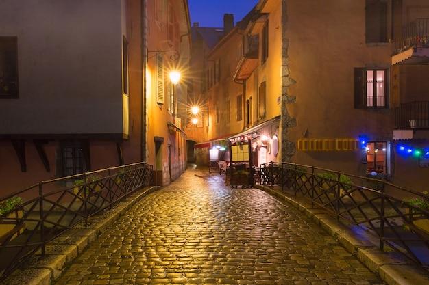 Bela rua e ponte sobre o rio thiou na cidade velha de annecy em noite chuvosa, frança