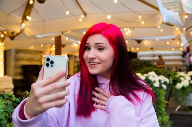 Bela ruiva blogueira influenciadora no café falando fazendo videochamada usando o smartphone com seus assinantes nas redes sociais.