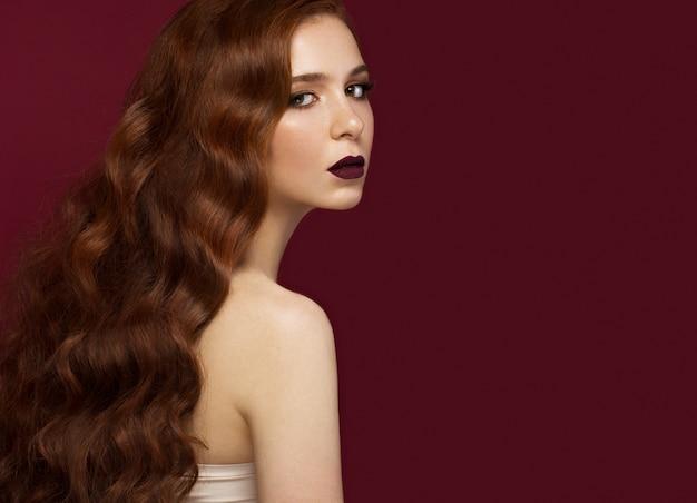 Bela ruiva com um cabelo perfeitamente ondulado e maquiagem clássica. rosto bonito.