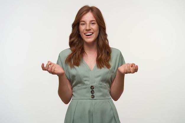 Bela ruiva feliz com um vestido vintage em cor pastel, sorrindo alegremente e levantando as palmas das mãos, isolada