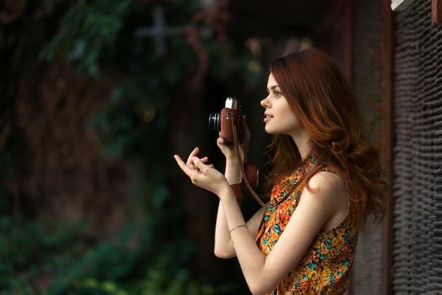Bela ruiva fotógrafo feminino tira fotos com uma câmera antiga