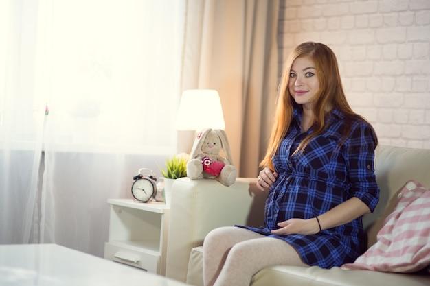 Bela ruiva jovem grávida sentada em casa no sofá e olhando pela janela, acariciando a barriga com um bebê.