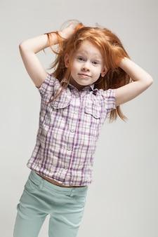 Bela ruiva menina na camisa xadrez, calças azuis brilhantes e botas brancas