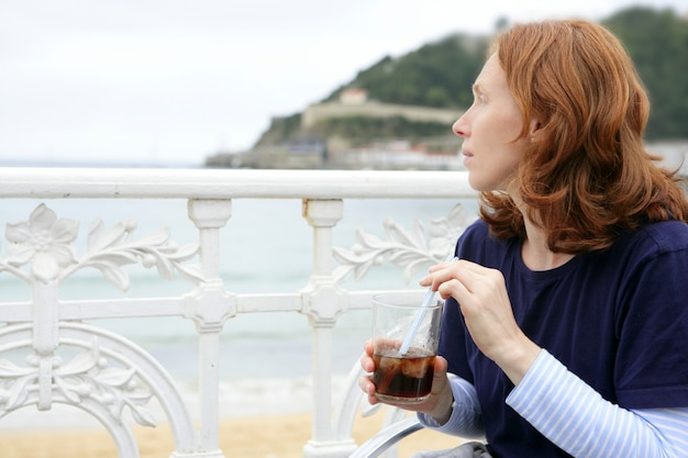 Bela ruiva mulher beber bebida