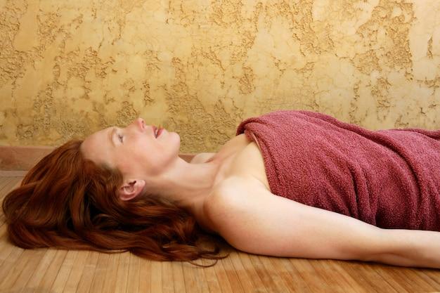 Bela ruiva mulher deitada no bambu no centro de spa dourado