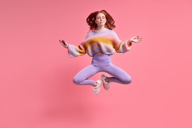 Bela ruiva pulando alto sentado em pose de lótus praticando ioga matinal, vestindo roupa casual isolado cor rosa pastel fundo retrato calmo mulher branca meditando