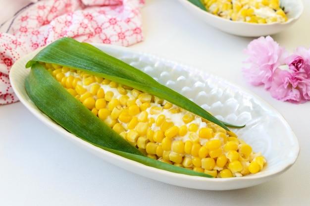 Bela salada em forma de milho para a mesa de férias. salada de milho, ameixas, queijo, ovos em pratos sobre um fundo claro.