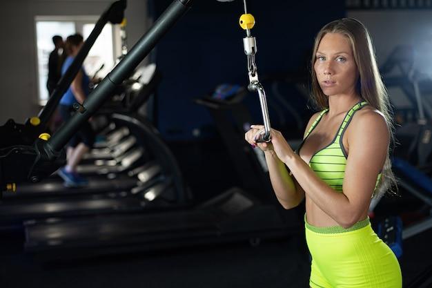 Bela sensual atlética jovem muscular. garota de aptidão caucasiana treina no ginásio