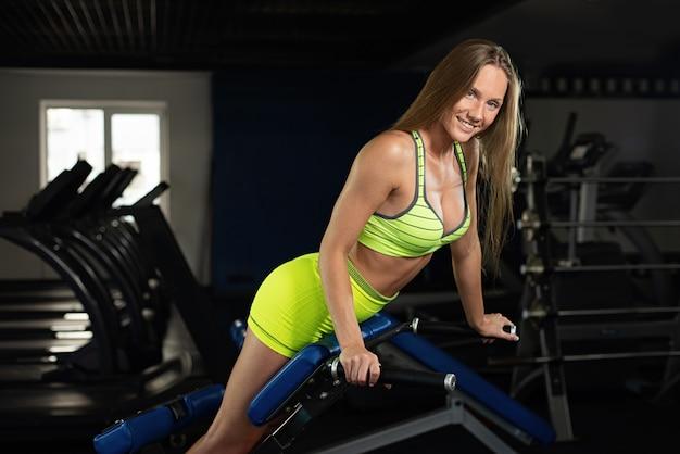 Bela sensual atlética jovem muscular. garota de aptidão treina no ginásio, a menina está descansando depois de um treino.