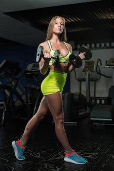 Bela sensual atlética jovem muscular. garota fitness treina no ginásio, fazendo exercícios com uma barra