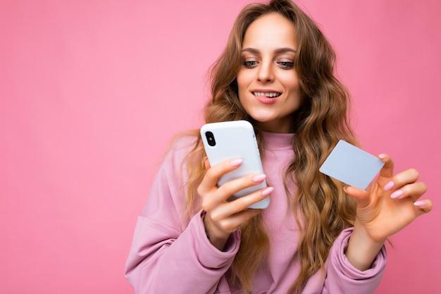 Bela sexy loira jovem loira encaracolada usando roupas cor de rosa isoladas sobre um fundo rosa