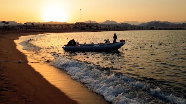 Bela silhueta de um barco a motor inflável balançando nas ondas do mar calmo contra o céu do pôr do sol