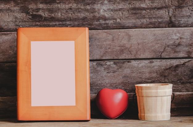 Bela simulação de moldura de madeira na prateleira decorada com coração dia dos namorados e cacto