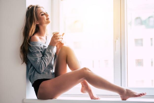 Bela sonhadora. mulher jovem e bonita segurando a xícara de café e mantendo os olhos fechados com um sorriso enquanto está sentada no parapeito da janela em casa