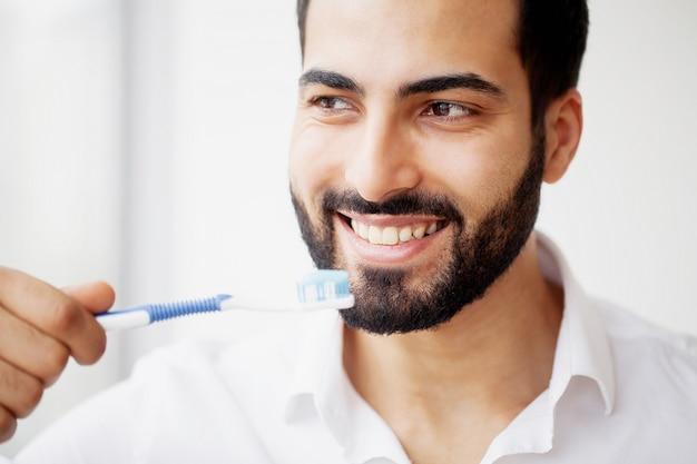 Bela sorrindo homem escovando os dentes brancos saudáveis com escova