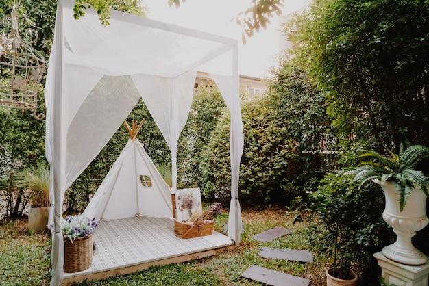 Bela tenda branca e decoração de acampamento no jardim de casa