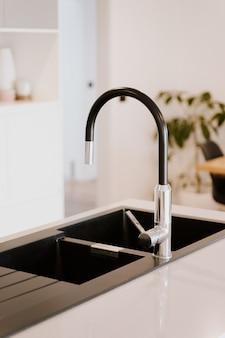 Bela torneira de estilo moderno com pia de aço na cozinha