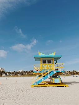 Bela torre de salva-vidas amarelo e azul claro sob um céu nublado e ensolarado em miami beach. flórida, eua Foto Premium