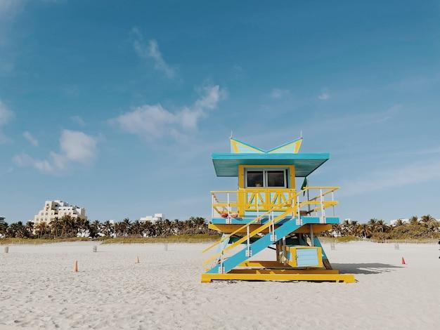 Bela torre de salva-vidas amarelo e azul claro sob um céu nublado e ensolarado em miami beach. flórida, eua