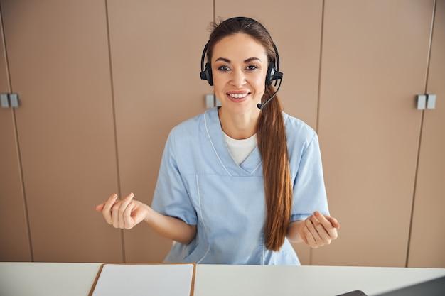 Bela trabalhadora médica em um fone de ouvido fazendo gestos com as mãos