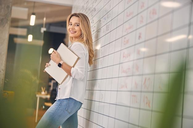 Bela trabalhadora sorrindo enquanto segura o caderno de desenho em espiral