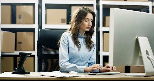 Bela trabalhadora trabalhando no computador no posto de entrega e digitando no teclado.