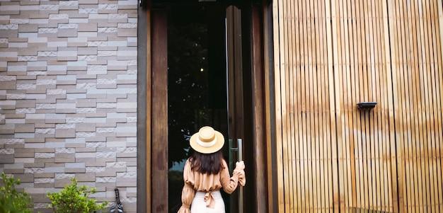 Bela turista abrindo a porta. mão feminina abrindo hotel