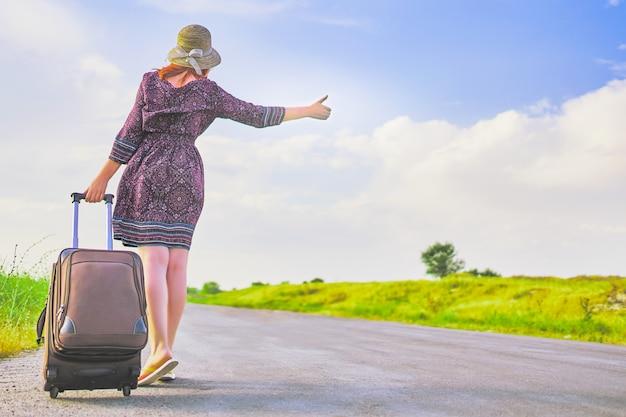 Bela turista feminina no vestido de verão e chapéu pedindo carona com mala na primavera