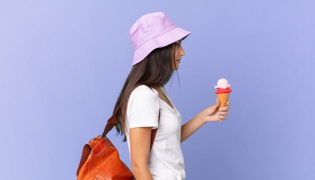 Bela turista hispânica em vista de perfil pensando, imaginando ou sonhando acordada e segurando um sorvete
