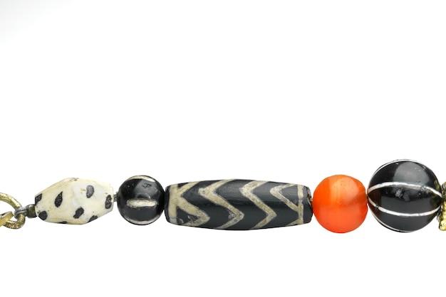 Bela variedade de ágata antiga gravada separada por um colar laranja redondo em forma de cornalina em um colar isolado no fundo branco, mianmar