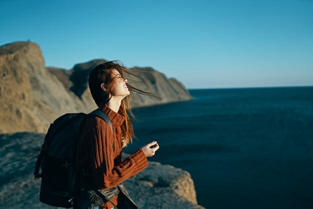 Bela viajante com uma mochila na natureza perto do mar
