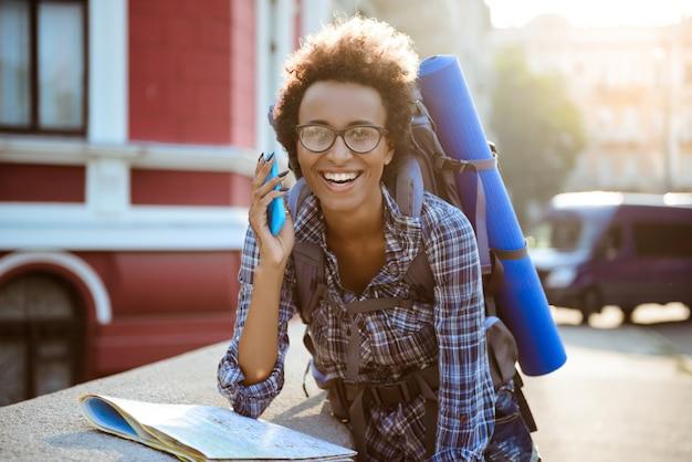Bela viajante feminino africano com mochila, falando no telefone, sorrindo.