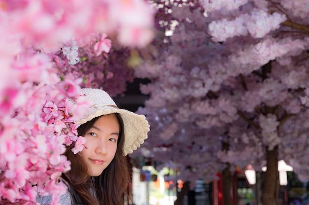 Bela viajante olhando e tocando flores de cerejeira