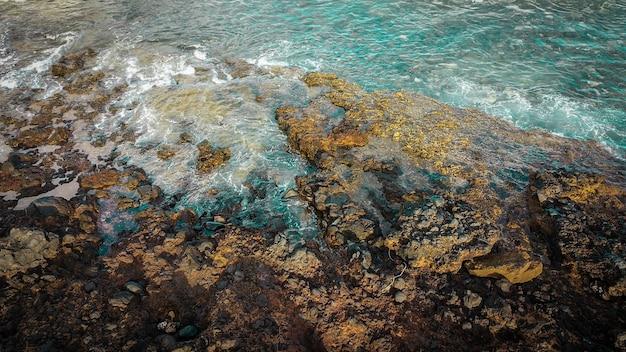 Bela vista aérea da onda do mar. cores azuis e espuma branca em uma água perigosa viva com a linha de costa de rochas e sem humanos