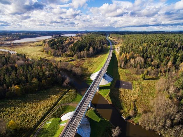 Bela vista aérea da ponte rodoviária sobre o rio, rodeado por floresta