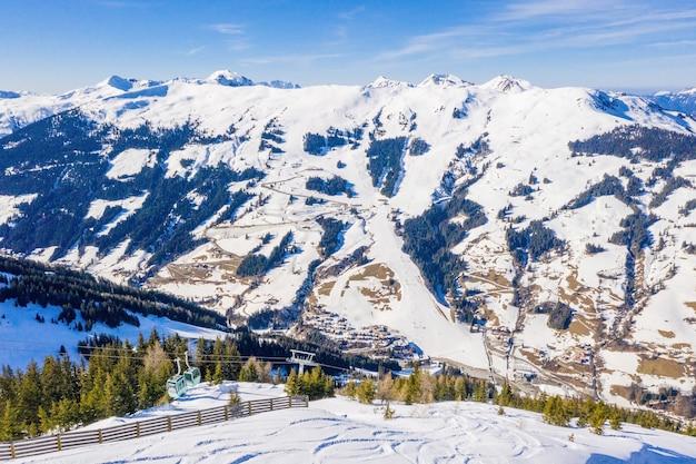 Bela vista aérea de uma estação de esqui e uma vila em uma paisagem montanhosa, nos alpes