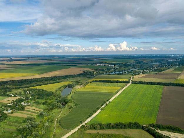 Bela vista aérea desde uma visão aérea para uma paisagem rural com uma vila, estrada de terra, rio, floresta e campos agrícolas de culturas plantadas no verão.